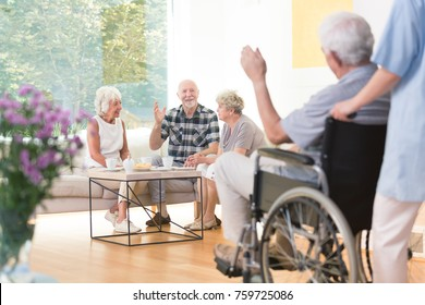 Group of senior people welcoming a friend while sitting together in living room
