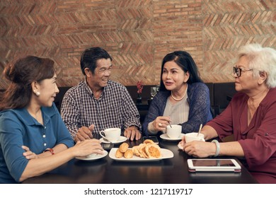 Group of senior Vietnamese people drinking tea with sweets and chatting in cafe