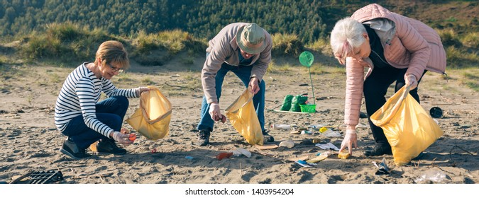 Group of senior volunteers picking up trash on the beach