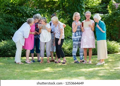 Group of senior women gladly looking at pictures and discussing them, standing in the park after art therapy lesson.