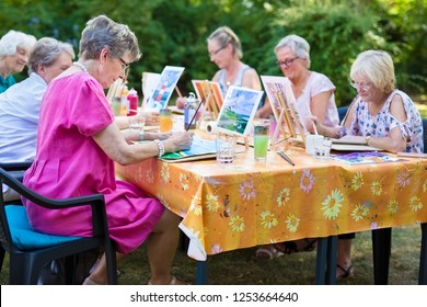 The group of senior women taking art lessons sitting outdoors at one table and learning together how to paint pictures.
