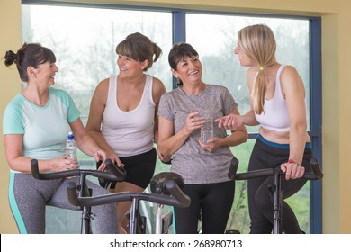 A group of senior women using spinning bikes at the gym