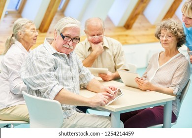 Group seniors in the computer course in the nursing home cared for by a caregiver