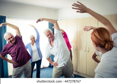Group of seniors doing exercises with nurse in the retirement house