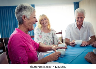 Group of seniors drinking coffee in the retirement house