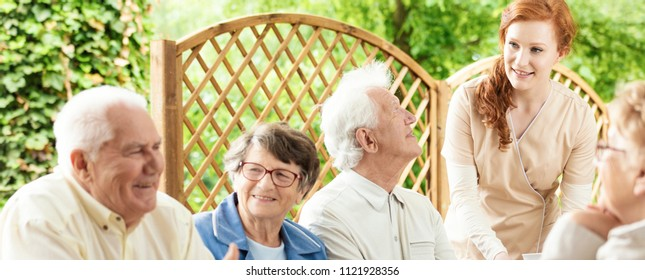 Group of seniors enjoying their time together outside in a garden of an assisted living home. A young volunteer helping. Panorama.