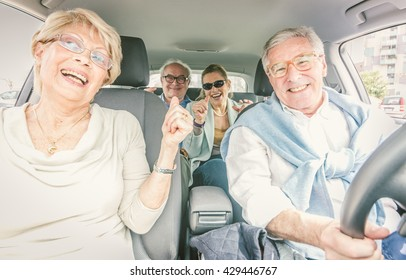 Group of seniors making party in the car while driving