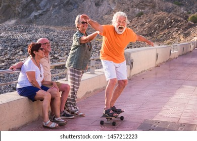 group of seniors and mature people at the beach have fun looking at old man riding a skateboard and laughing with scare face - woman touching the man