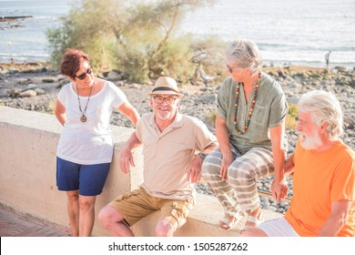 group of seniors and mature people sitted at the beach on a bench - happy friendship with two couples of married pensioner talking and having fun