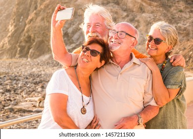 group of seniors and mature people taking a selfie together at the beach with the rocks on the backround -- having fun together at the sunet