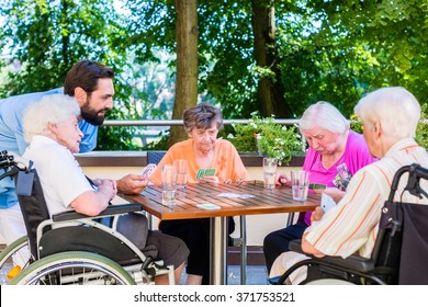 Group of seniors and nurse playing cards in rest home