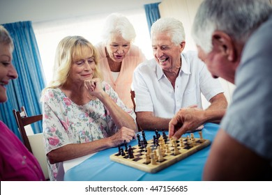 Group of seniors playing chess in the retirement house