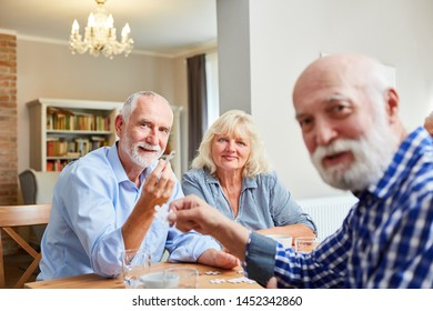 Group of seniors playing puzzle together in retirement home or apartment
