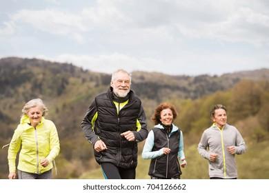 Group of seniors running outside on green hills.
