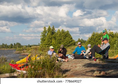 A group of seniors in sea kayaks camping and paddling on the Great Lakes in northern Canada.