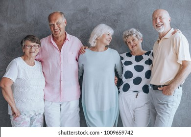 Group of seniors smiling and standing in a room with grey texture wall