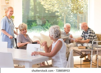 Group of seniors spending free time in bright living room with big window at nursing house