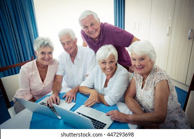 Group of seniors using a computer in the retirement house