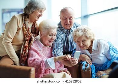 Group of seniors using mobile phone