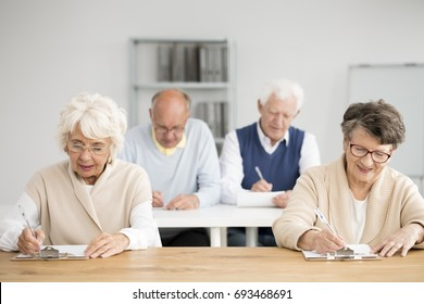 Group of seniors writing an IT test in white classroom
