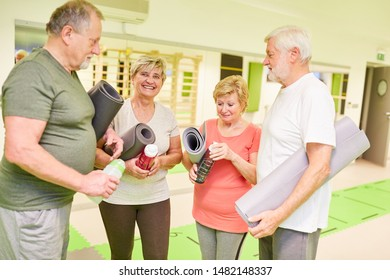 Group of seniors with yoga mat in the fitness center during a break during small talk