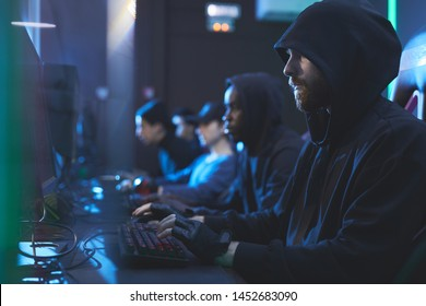 Group of serious gloomy young hackers in hoodies sitting in row and typing on keyboards fastly in server room