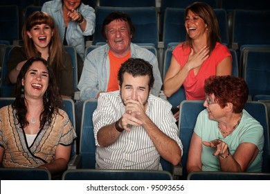 Group of seven audience watching movie laugh in theater