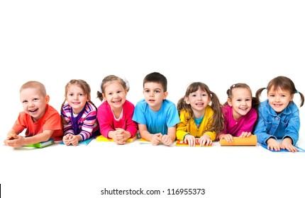 Group of seven children are lying on floor with copybooks together