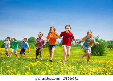 Group of seven happy running in the park kids, boys and girls, black and Caucasian