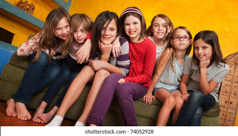 Group of seven little girls seated on a couch