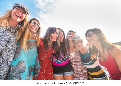 group of seven nice and beautiful caucasian girls young women have fun and laugh and smiles outdoor during the sunset. backlight people enjoying the friendship hugging each other