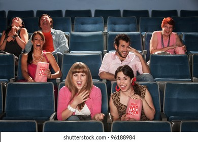 Group of seven people laughing out loud in a theater