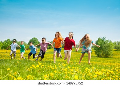 Group of seven running in the park kids, boys and girls, black and Caucasian