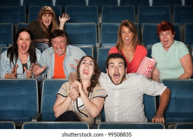Group of seven scared people screaming in a theater