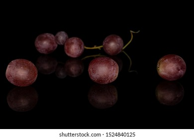Group of seven whole fresh purple grape rose isolated on black glass