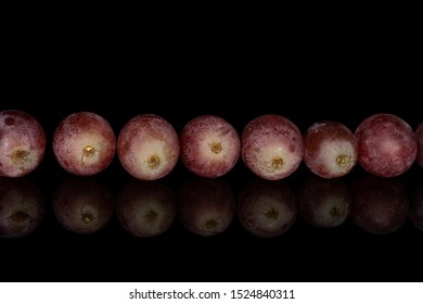 Group of seven whole fresh purple grape rose in row isolated on black glass