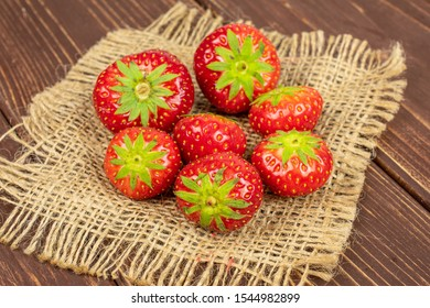 Group of seven whole fresh red strawberry on natural sackcloth on brown wood