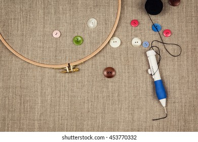 Group of sewing objects lying flat on a natural linen background. Horizontal background for ad or packaging.