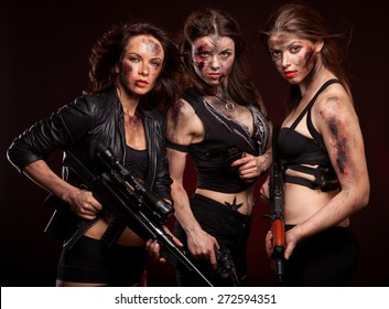 Group of sexy woman like riot woman. Girls with weapon, gun, rifle and knife. With blood on face.