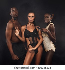 Group of a sexy young people black and white. Fashion, beauty, entertainment. Two beautiful women in erotic swimsuit with standing beside man.