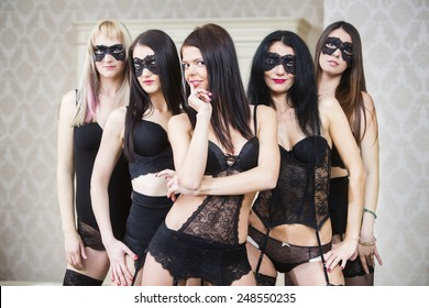 Group of sexy young woman in black lingerie, stockings and face mask in hotel room. Getting ready for strip-plastic performance.