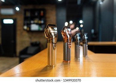 Group of shiny metallic hair trimmers stands in a modern men's barbershop on the table. Vintage hairdressing machines.