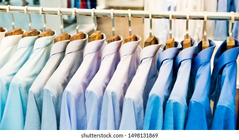Group of shirts hanging on rack in a row.