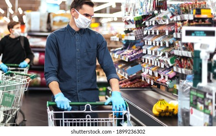 group of shoppers in protective masks standing near the checkout in a supermarket