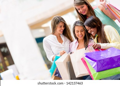 Group of shopping girls looking at their purchases