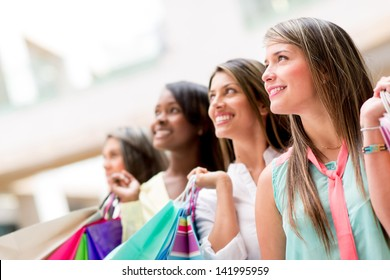 Group of shopping  women carrying bags and smiling