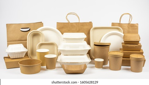 Group shot of biodegradable and recyclable food packaging on white background, paper plates, cups, containers, bags, no logos