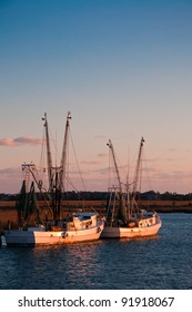 A Group of Shrimping Boats Wait at the Dock in the Evening