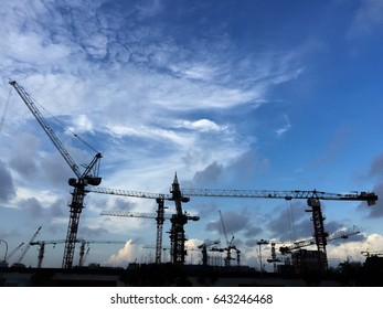 A group of silhouette construction cranes at work site against blue sky and white dark clouds.