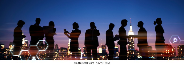 Group of silhouetted business people talking at night